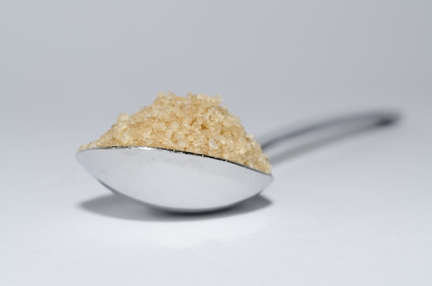 Primer plano de una cucharada de azúcar morena sobre la superficie blanca