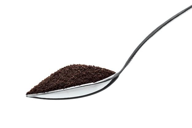 Primer plano de una cucharadita llena de té de polvo negro