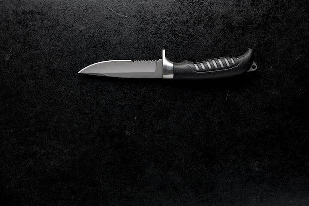 Primer plano de un cuchillo afilado fijo sobre una mesa negra