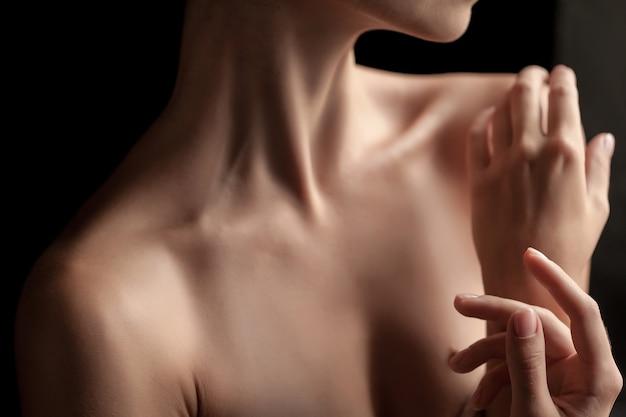 El primer plano del cuello y las manos de una mujer joven sobre fondo oscuro