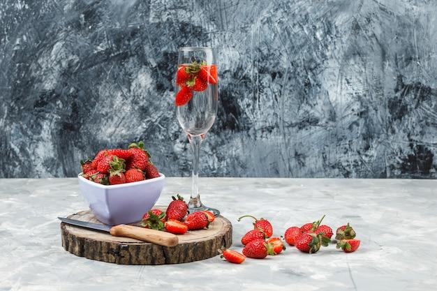 Primer plano de un cuenco de fresas sobre tabla de madera con un vaso de bebida en la superficie de mármol blanco y azul oscuro. horizontal