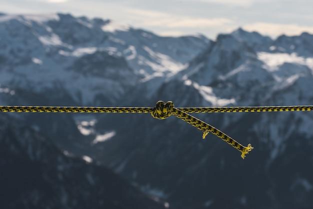 Primer plano de una cuerda torcida frente a las montañas cubiertas de nieve