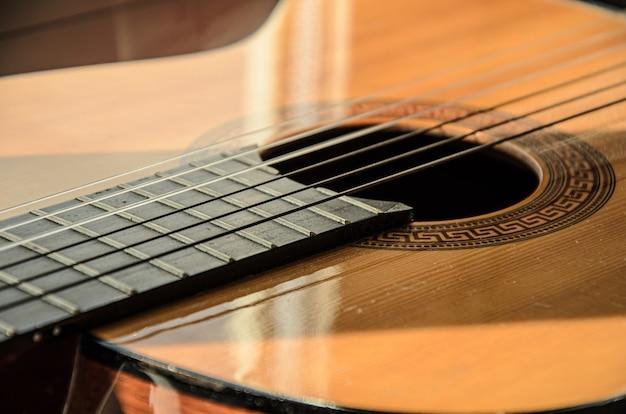 Primer plano de cuerdas de guitarra a la luz del sol. guitarra acústica de madera de seis cuerdas, instrumento musical de cuerda.