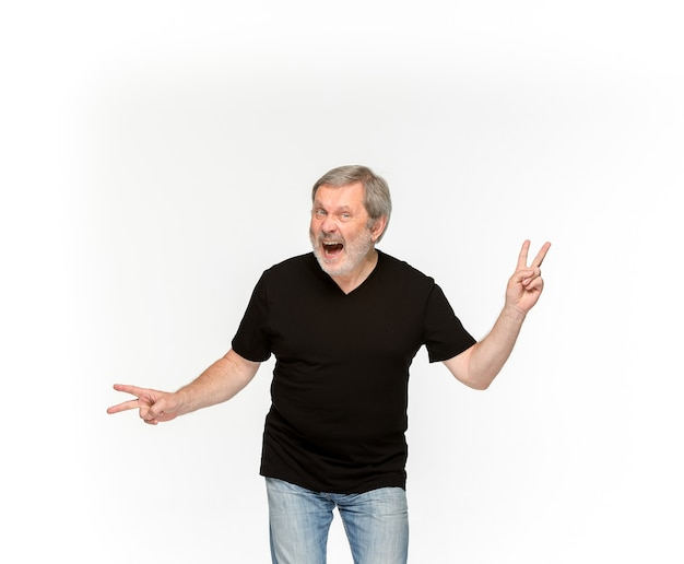 Primer plano del cuerpo del hombre mayor en camiseta negra vacía aislada sobre fondo blanco. ropa, maqueta para el concepto de diseño con espacio de copia.