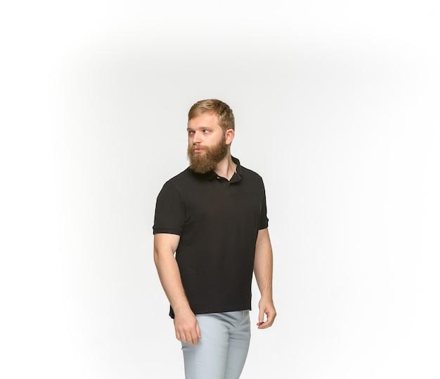 Primer plano del cuerpo del joven en camiseta negra vacía sobre blanco.