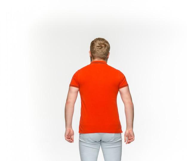 Primer plano del cuerpo del joven en camiseta roja vacía aislado en blanco