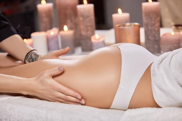 Primer plano de culo de mujer bonita con masajista masaje de piernas en spa