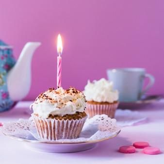 Primer plano de cupcake con vela encendida en cumpleaños