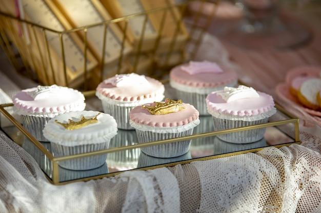 Primer plano de cupcakes rosados y blancos en una bandeja sobre la mesa