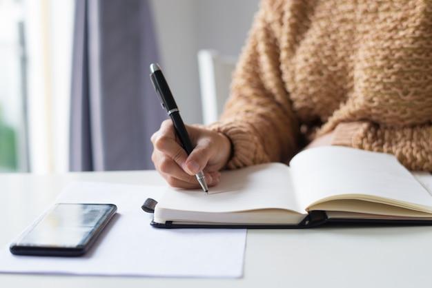 Primer plano de una dama irreconocible haciendo notas