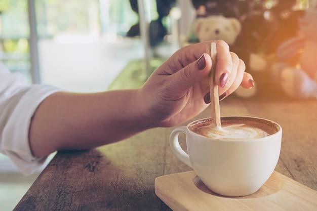 Primer plano de dama preparando y comiendo una taza de café caliente