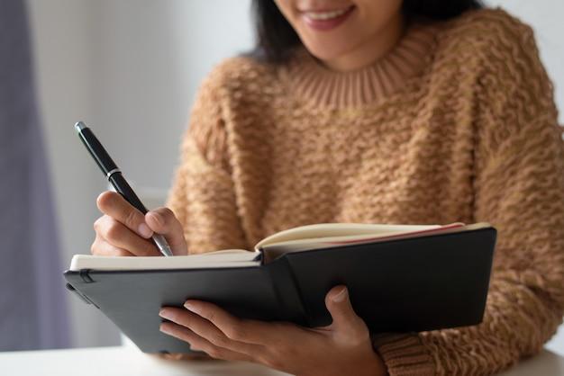 Primer plano de dama sonriente haciendo notas sobre ideas en el diario