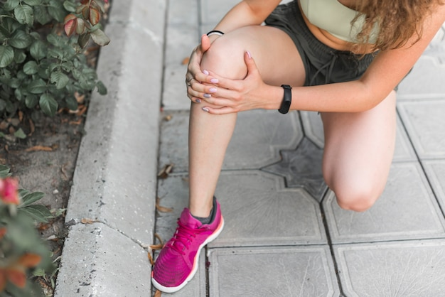 Primer plano de atleta femenina con dolor de rodilla