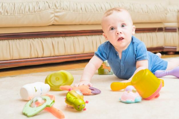 Primer plano de bebé jugando con juguetes coloridos en la alfombra