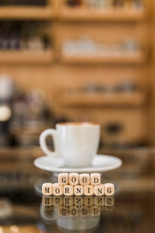 Primer plano de buenos días bloques cúbicos con taza de café en la superficie de vidrio