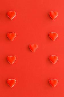 Primer plano de caramelos dulces en forma de corazón sobre superficie roja