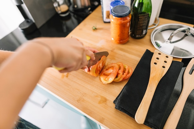 Primer plano, de, corte de mano, rebanadas de tomate, con, cuchillo