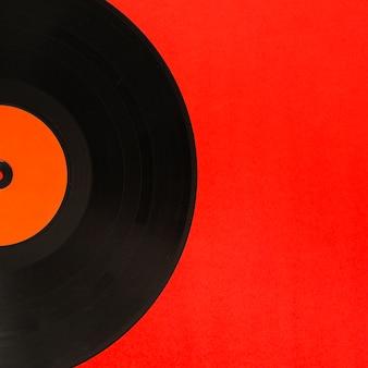 Primer plano de disco de vinilo sobre el fondo rojo