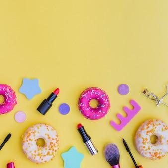 Primer plano de donuts; lápiz labial; rizador de pestañas; cepillo de maquillaje y separador de dedos sobre fondo amarillo