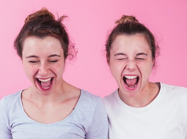 Primer plano de dos amigas gritando contra el fondo rosa