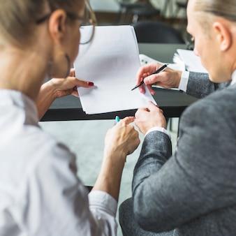 Primer plano de dos empresarios comprobando el documento en el restaurante