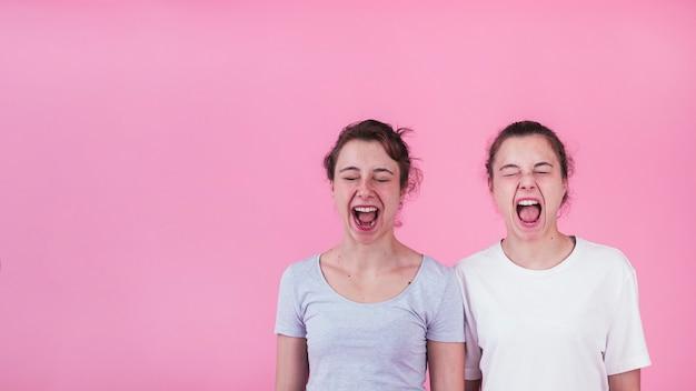 Primer plano de dos hermanas gritando contra el fondo rosa