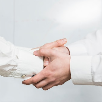 Primer plano de dos socios estrechándole la mano