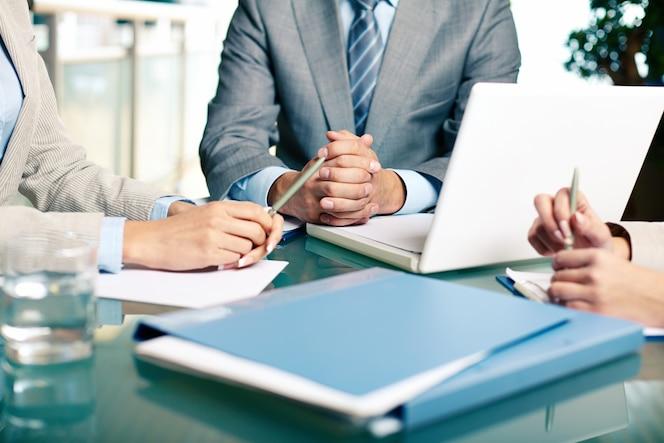 Primer plano de ejecutivos sentados en la mesa