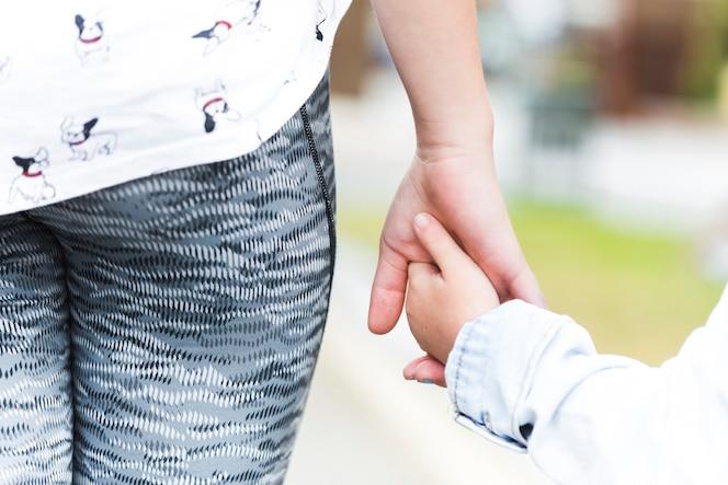 Primer plano de hermano y hermana cogidos de la mano