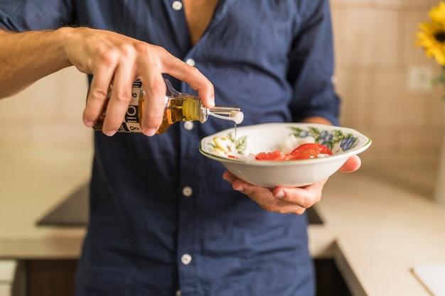 Primer plano, de, hombre, aderezo, el, ensalada, con, aceite de oliva, en, el, tazón