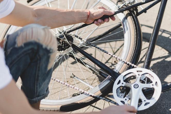 Primer plano de hombre arreglando la cadena de bicicleta