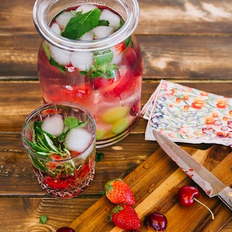 Primer plano de jugo saludable con ingredientes y cubitos de hielo en tarro