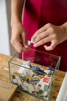 Primer plano de la mano de la mujer con papel rasgado sobre el recipiente de vidrio