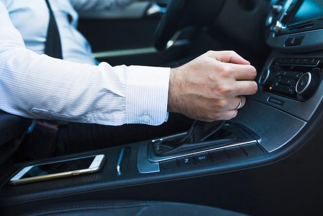 Primer plano de la mano de un hombre cambio de marcha en el coche
