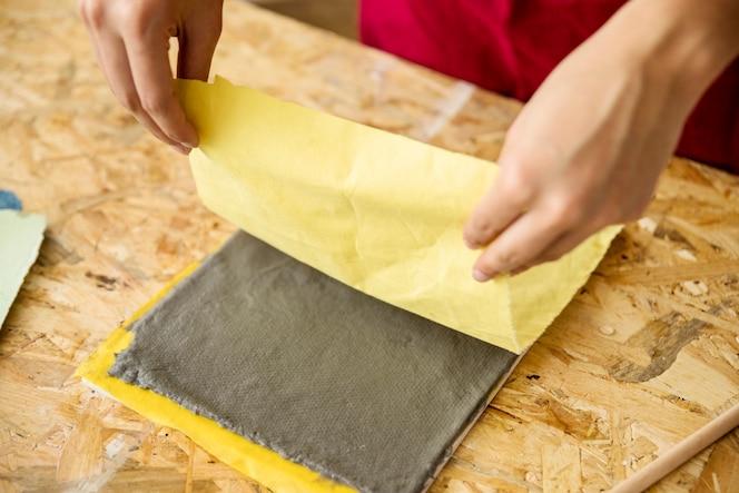Primer plano de la mano de una mujer que sostiene la tela amarilla sobre la pulpa de papel