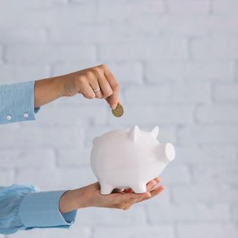 Primer plano de la mano de una persona insertando moneda en piggybank blanco