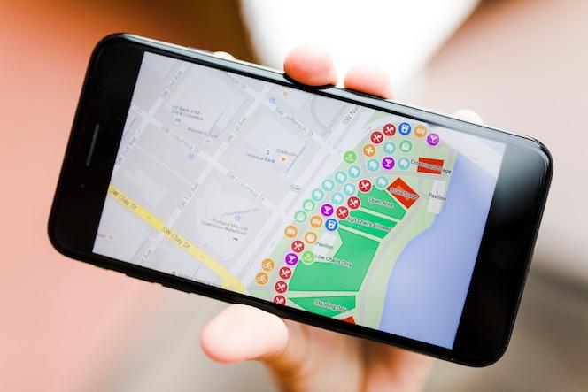 Primer plano de la mano de una persona que sostiene el teléfono inteligente con el mapa de navegación gps