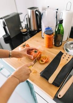Primer plano de la mano del hombre cortar rodajas de tomate en el mostrador de la cocina