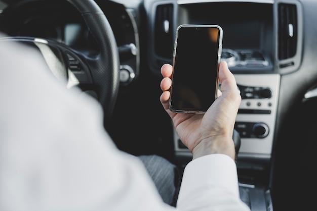 Primer plano de la mano del hombre que sostiene el teléfono móvil con pantalla en blanco en el coche