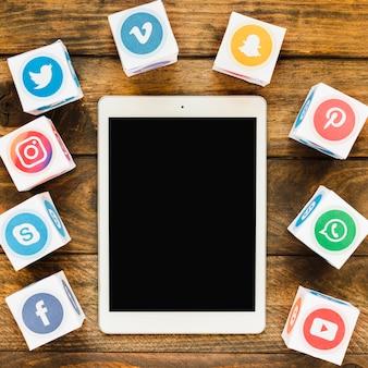 Primer plano de la tableta digital en blanco con caja de iconos de redes sociales