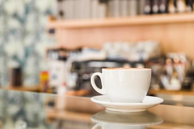 Primer plano de la taza de café en el mostrador de vidrio