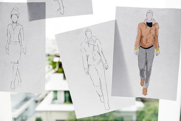 Primer plano de los papeles del diseño del bosquejo de la moda en el vidrio