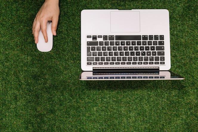 Primer plano de mano sosteniendo el ratón con la computadora portátil abierta sobre fondo de hierba falsa
