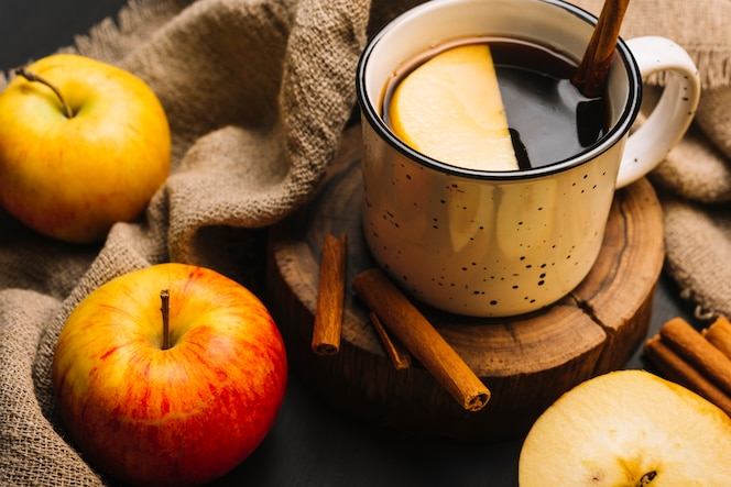 Primer plano de manzanas y tela cerca de bebidas con especias