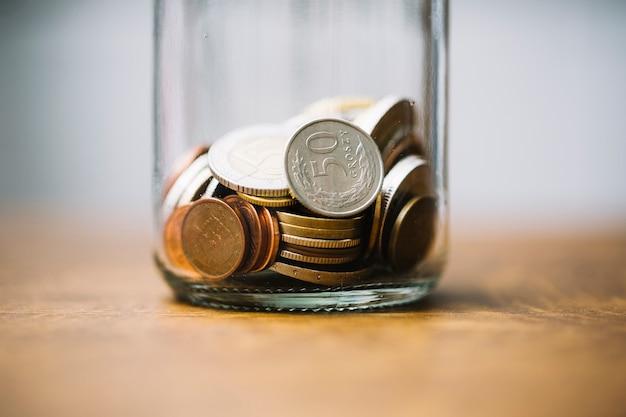 Primer plano de monedas recogidas en el frasco de vidrio en la mesa