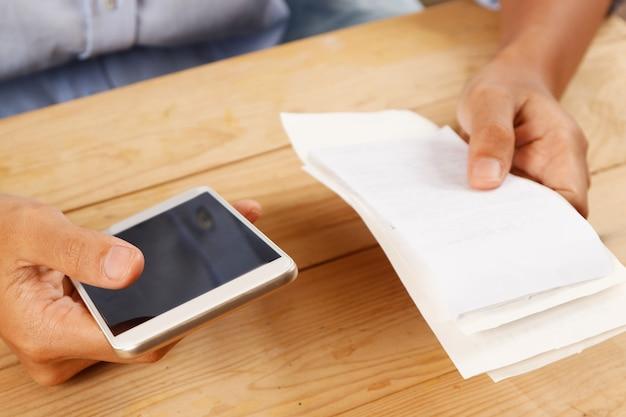 Primer plano de mujer calculando o pagando facturas