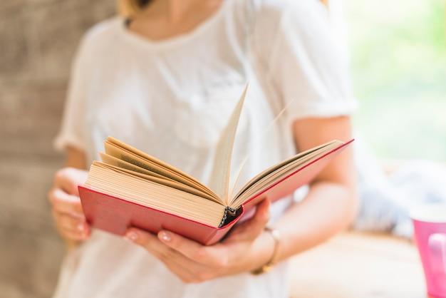 Primer plano de mujer con libro de tapa roja en las manos