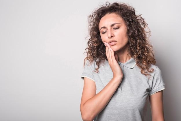 Primer plano de mujer con pelo rizado que sufre de dolor de muelas sobre fondo gris