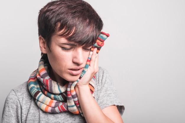 Primer plano de mujer enferma con dolor de muelas sobre fondo gris