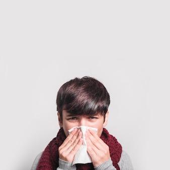 Primer plano de mujer estornudando con tejido sobre fondo blanco